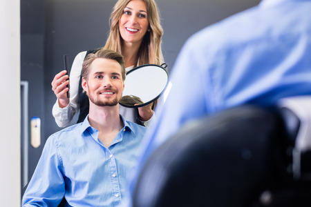 haircutter: Haircutter showing customer the new cut Stock Photo