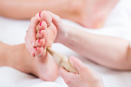 massaged: Women at reflexology having foot massaged or pressed with wooden stick