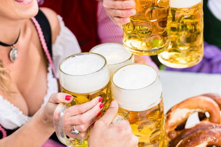 tracht: Clinking glasses with beer in Bavarian pub