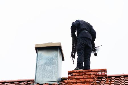 自宅の屋根の上の煙突掃除人立っています。