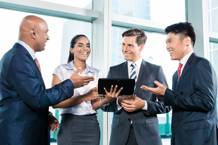informal: Informal business people with table computer discussing in front of window to the city skyline Stock Photo