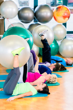 Men exercise: Young and senior people exercising with ball in gym, diversity group