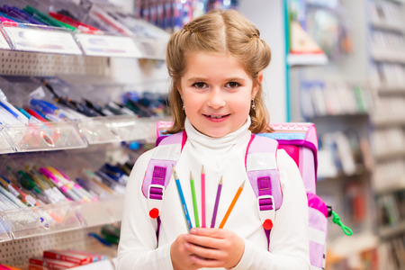 happy family shopping: Student in stationery store buying pens holding them into the camera