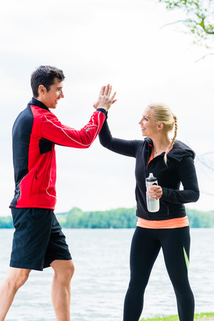 couple outdoor: Woman and man at break from running giving each other a high five Stock Photo