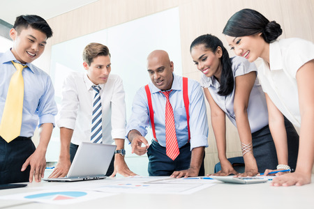 rolled up sleeves: Asian business team in strategy meeting bowing on desk over with graphs and numbers Stock Photo