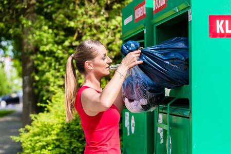 Woman at clothes recycling skip Foto de archivo