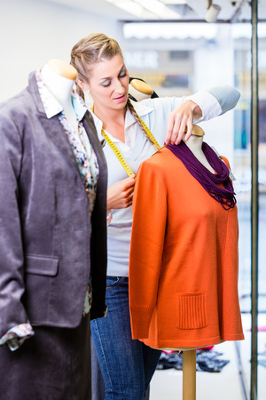 merchandiser: Small business owner dressing shop window putting new fashion clothes on mannequin