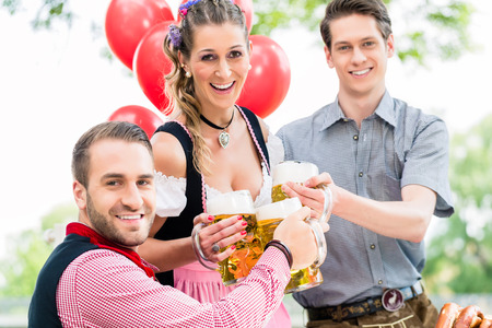 tracht: Three friends in Munich Beer garden clinking glasses wearing traditional Tracht Stock Photo