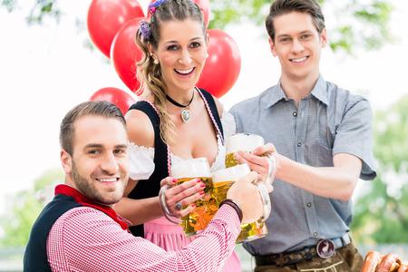beer garden: Three friends in Munich Beer garden clinking glasses wearing traditional Tracht Stock Photo