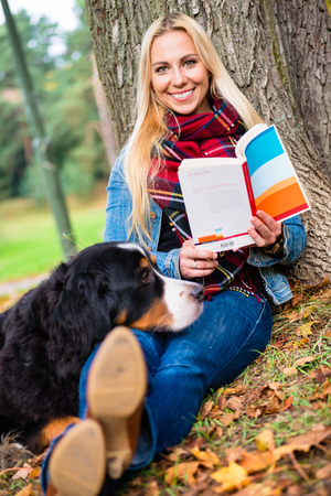 bernese mountain dog: Woman with her Bernese mountain dog reading book in autumn park sitting on meadow covered with foliage