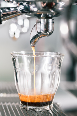 with coffee maker: Espresso running in glass on professional coffee maker