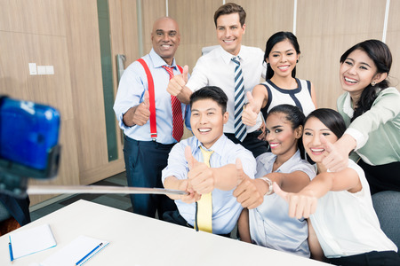 asian group: Business team taking picture with selfie stick