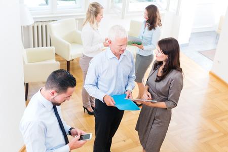 personas de pie: Grupo de hombres de negocios de pie en el cargo, discutiendo y trabajando juntos