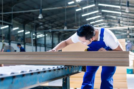 carpintero: Carpintero en madera asiática taller de trabajo en los tablones de ponerlos en la sierra