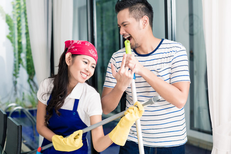 air guitar: Indonesian couple having fun cleaning the home, woman and man playing air guitar on duster and broom