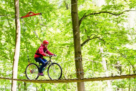 aventura: Muchacha en la bicicleta en la plataforma en alta parque de cuerdas