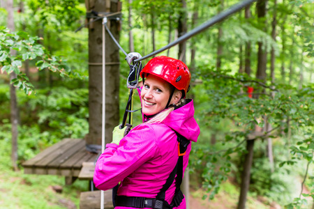 courses: Woman in high rope course or park climbing Stock Photo