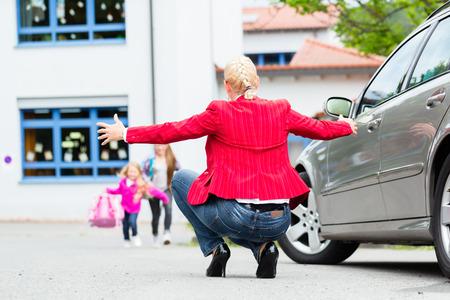 bringing: Mother hugging child after bringing her to school