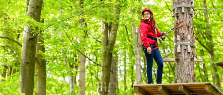 course: Teenager girl climbing in high rope course or parl Stock Photo
