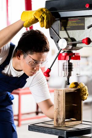 diligente: Trabajador en la máquina de perforación de trabajo taller sobre una caja de madera