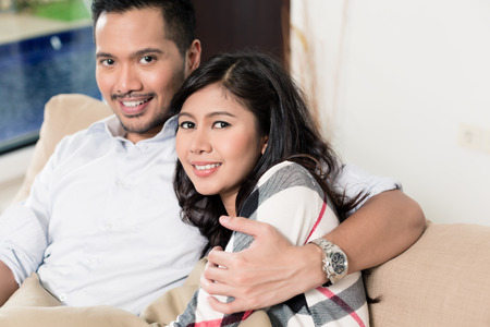 pretty young girl: Asian couple cuddling on sofa in living room
