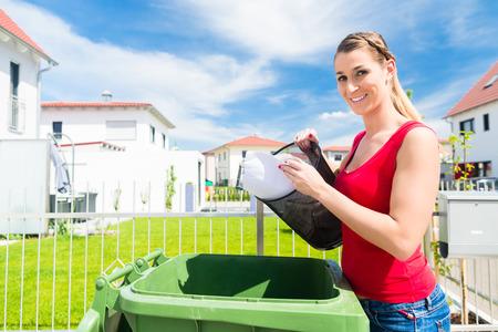 basura: Mujer vaciando basura o basura en caja de arena