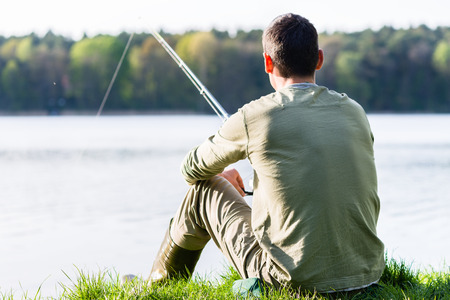 fishing scene: Angler sitting in grass at lake fishing with his rod, a very peaceful scene