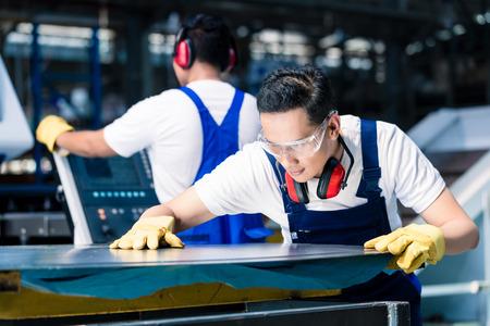 Team van werknemers met metalen platen op snijder in Aziatische fabriek