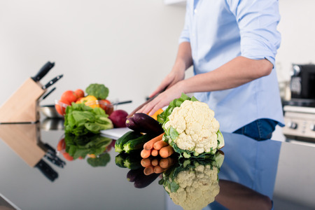 countertop: Man cooking and preparing salad in kitchen Stock Photo