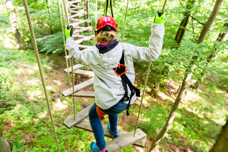 courses: Girl seen from above climbing in high rope course Stock Photo