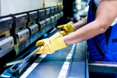 acier: Travailleur asiatique en usine à la machine de saut de métal mettant pièce dans