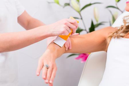 depilacion con cera: Mujer que recibe la depilaci�n con cera para la depilaci�n en sal�n de belleza
