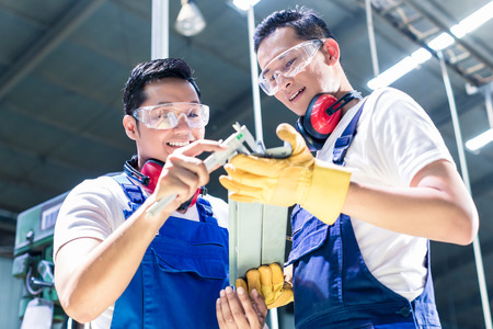 Two industrial workers inspecting work piece standing on the factory floor with ear muffs and goggles