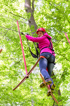 tree  forest: Woman in high rope course or park climbing Stock Photo