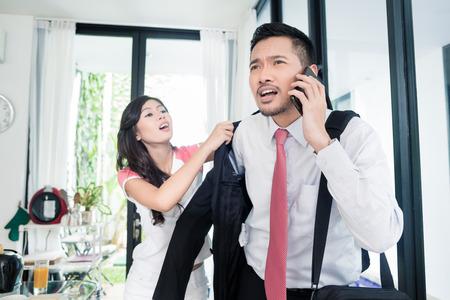 Vrouw helpen man te laat voor het werk in de jas, het paar is in een haast