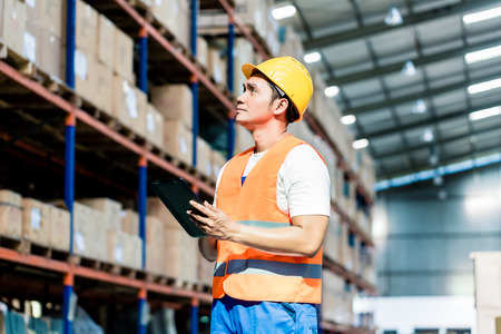 Worker taking inventory in logistics warehouse