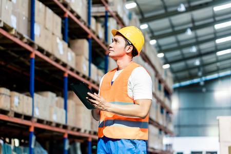 ref: Trabajador hacer un inventario en almacén logístico