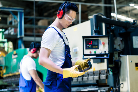 Asian machine operator in production plant checking data Standard-Bild