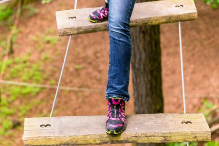 rope bridge: Girl doing step on rope bridge Stock Photo