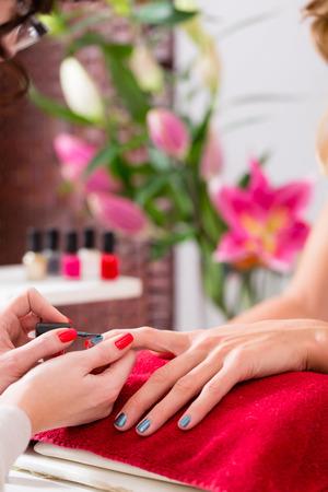 salon beaut�: Femme recevant manucure dans un salon de beaut�, ses ongles en cours de polissage