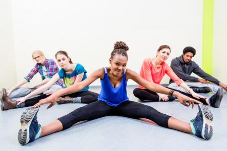 fitness hombres: La gente joven que estira las piernas en el gimnasio de la gimnasia Foto de archivo