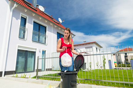 basura: Mujer tirar la basura en el contenedor de distancia Foto de archivo