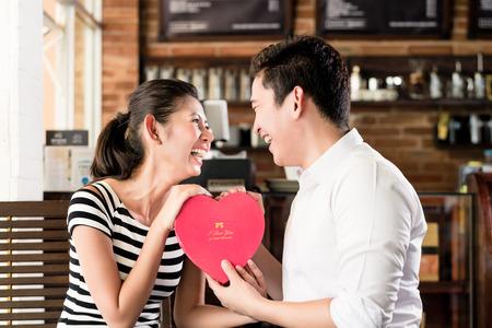 anniversary: Asia pareja, mujer y hombre, que ten�a fecha en la cafeter�a con el coraz�n rojo, el coqueteo o la celebraci�n de aniversario Foto de archivo