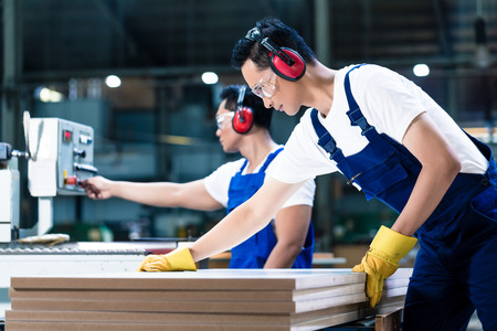 factory: Two wood workers in carpentry cutting boards putting them in saw Stock Photo