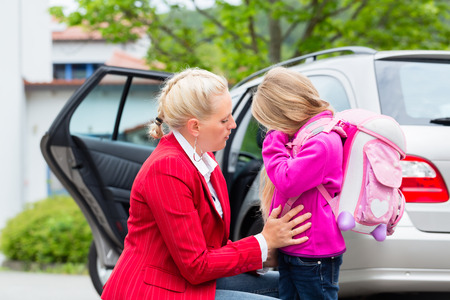 fear child: Mother consoling daughter on first day at school, the kid being a bit afraid of what may lay ahead