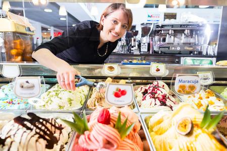 Vendeur présentant la crème glacée dans l'affichage de salon