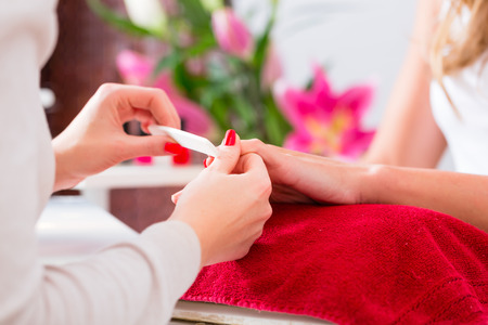 parlor: Woman getting manicure in nail parlor with file, close shot