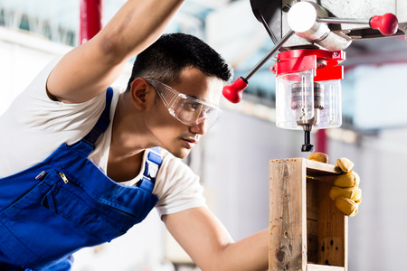 drilling machine: Asian worker on drilling machine in production factory or manufacturing plant Stock Photo