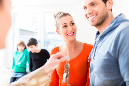 accommodation: Accommodation broker giving home key to family Stock Photo