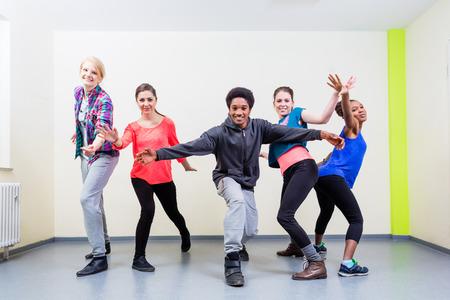 Groep jonge mensen die dansles in de gymzaal